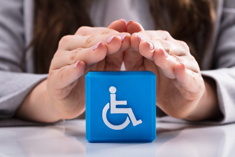 Ręce ułożone w osłaniający daszek nad symbolem osoby niepełnosprawnej