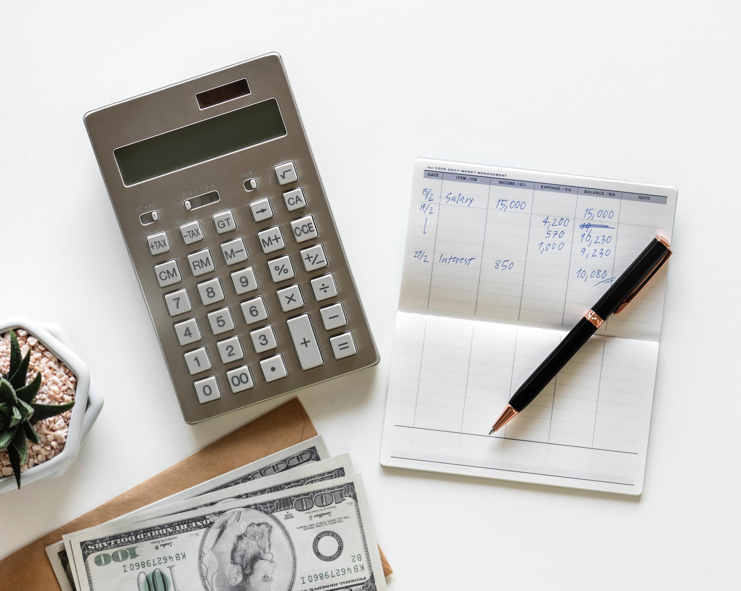 Kalkulator, plik banknotów i notes z zyskami